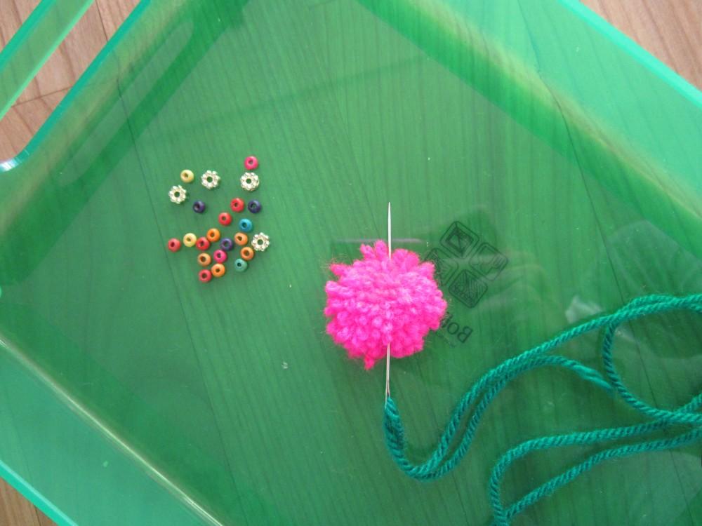 DIY Bommelkette - Bommel abwechselnd mit Perlen auf Faden ziehen