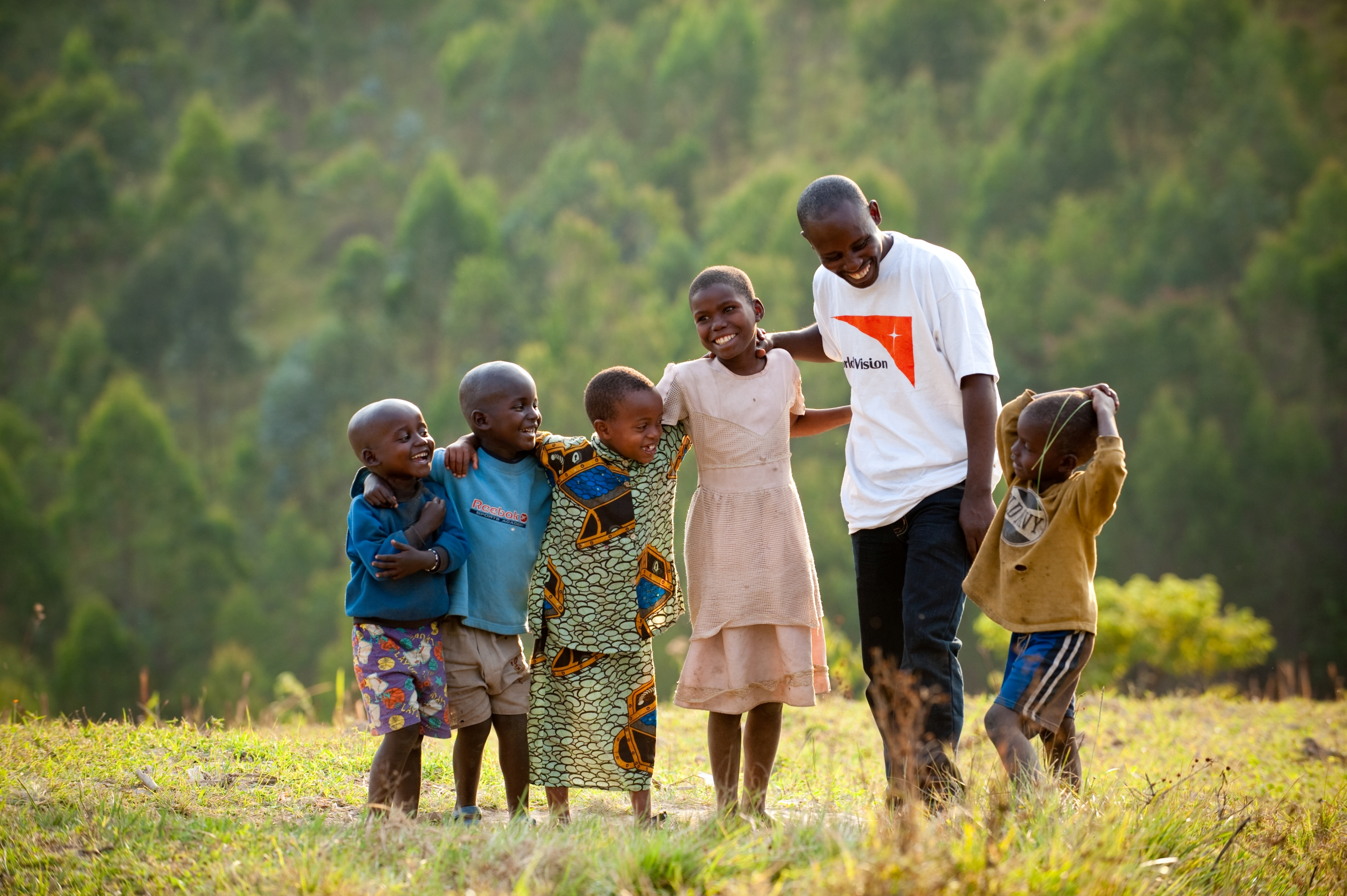 Jean Marie Mugwaneza, 36, World Vision Customer Relations for Nyaruguru ADP, Rwanda, with children in the ADP. He was among the first to register children for sponsorship in the ADP, and continues to live and work in the community.