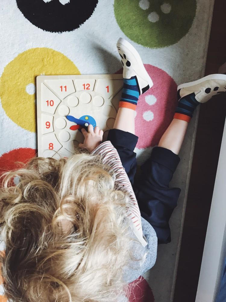 Kind mit Spielzeug beim Uhrzeit lernen